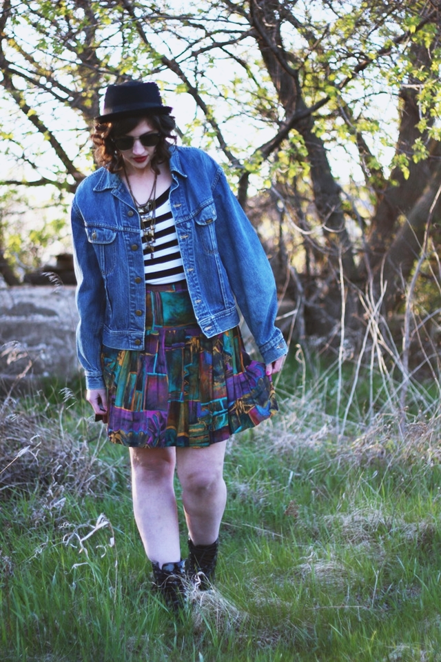Striped top, colorful skirt, denim jacket, fake Doc Martens, and dark lips.