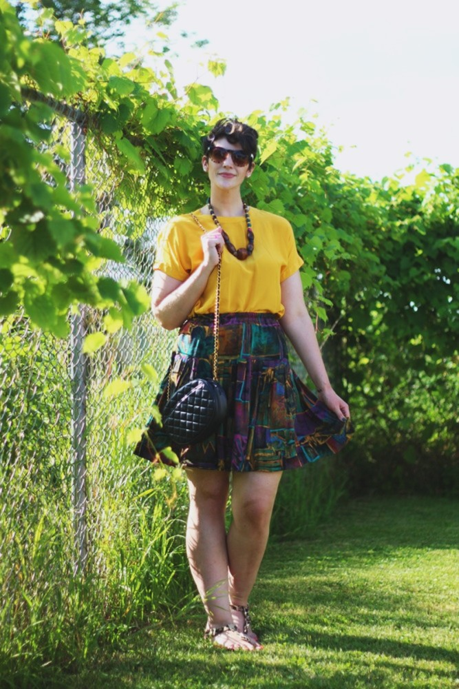 Outfit: Yellow blouse, multicolor skirt, thrifted quilted purse, beaded necklace.
