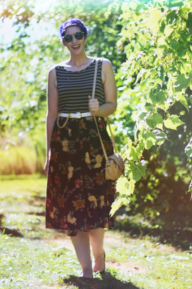 Fall outfit details: Striped tank top, dark floral print skirt, small beige purse, white and gold lion head belt, purple pixie haircut