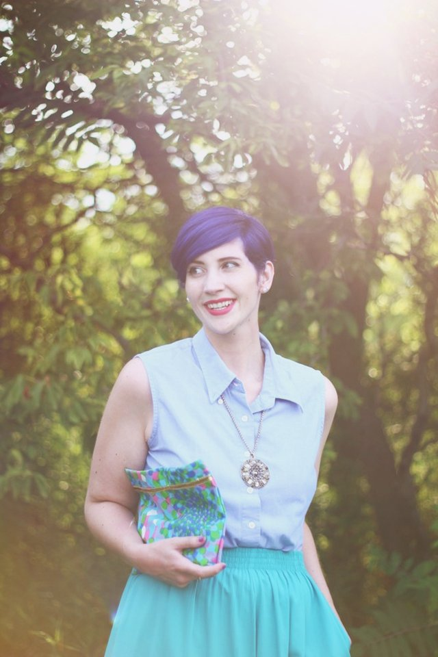 Purple pixie cut, gold medallion necklace, vintage patterned clutch
