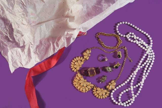 Pile of thrifted vintage jewelry on purple background