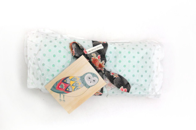 Secret Santa gift wrapped in white glitter polka dot tissue paper, tied with floral fabric in a bow, and artsy owl greeting card
