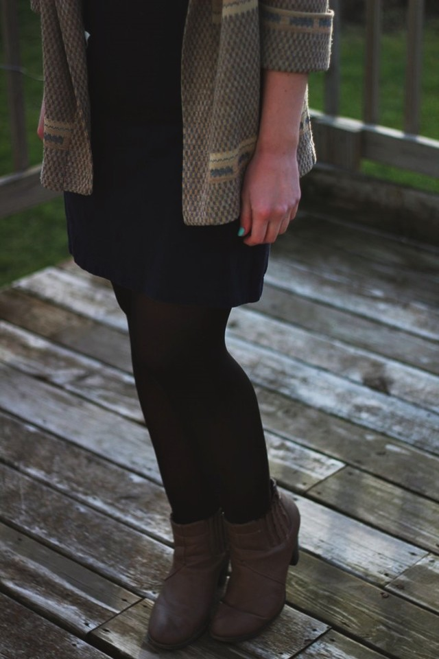 outfit: black high neck early 2000's dress, black tights, camel tan heeled booties, vintage patterned cardigan