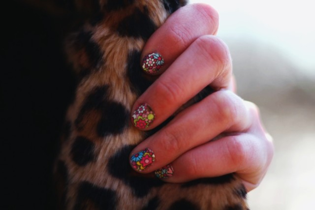 Sally Hansen floral nail stickers for spring against a leopard print coat.
