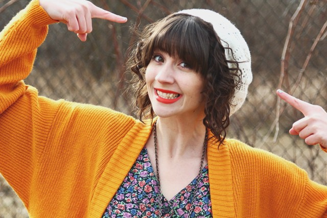 Curly brown hair and a white slouchy knit hat. Bright outfit with orange lipstick.