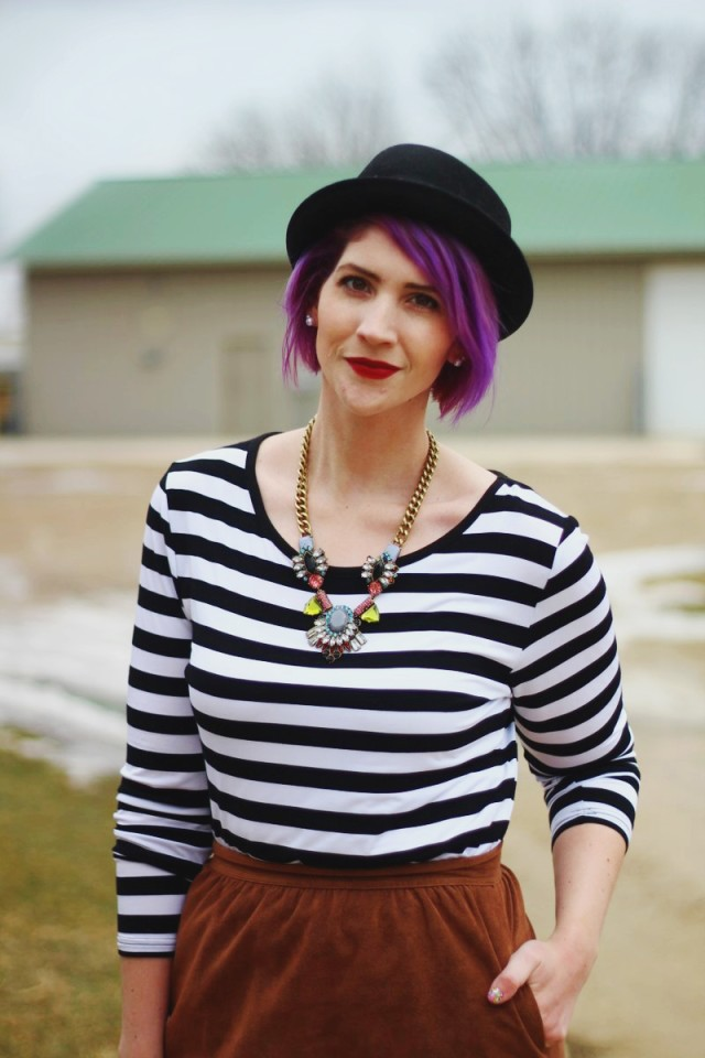 Outfit: striped top, brown suede skirt, statement necklace, red lip, black pork pie hat, purple hair
