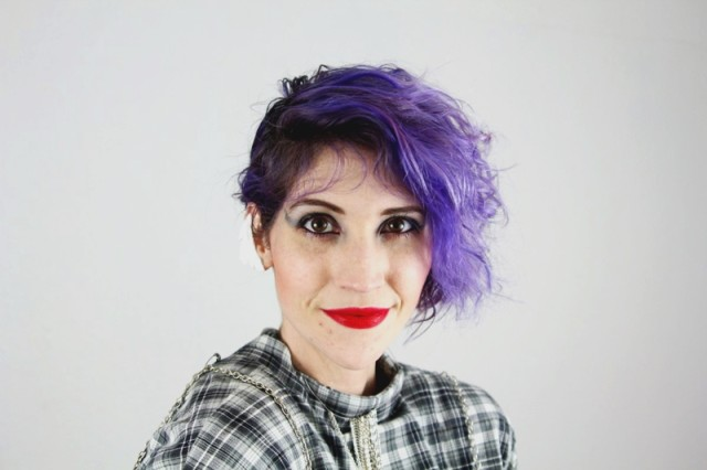 A Cyndi Lauper look inspired by 1980's fashion, curly purple hair and red lipstick