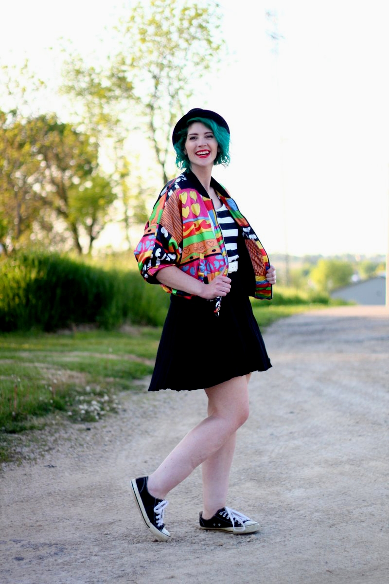 Outfit: brightly patterned jacket, striped top, black skirt, thick white belt, green hair, pork pie hat, red lipstick, black sneakers