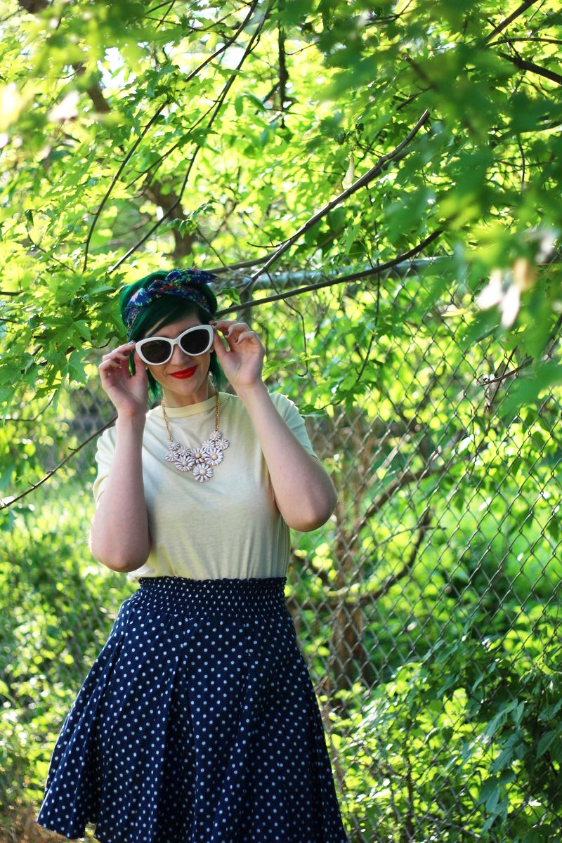 Outfit: primary colors, yellow t-shirt, navy blue polka dot skirt, floral headscarf, flower bib necklace, red lipstick