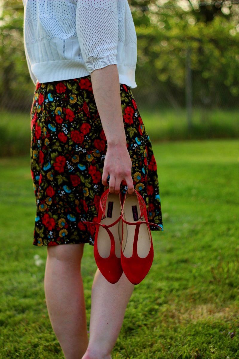 Outfit details: black floral skirt, white cardigan, red t-strap flat shoes