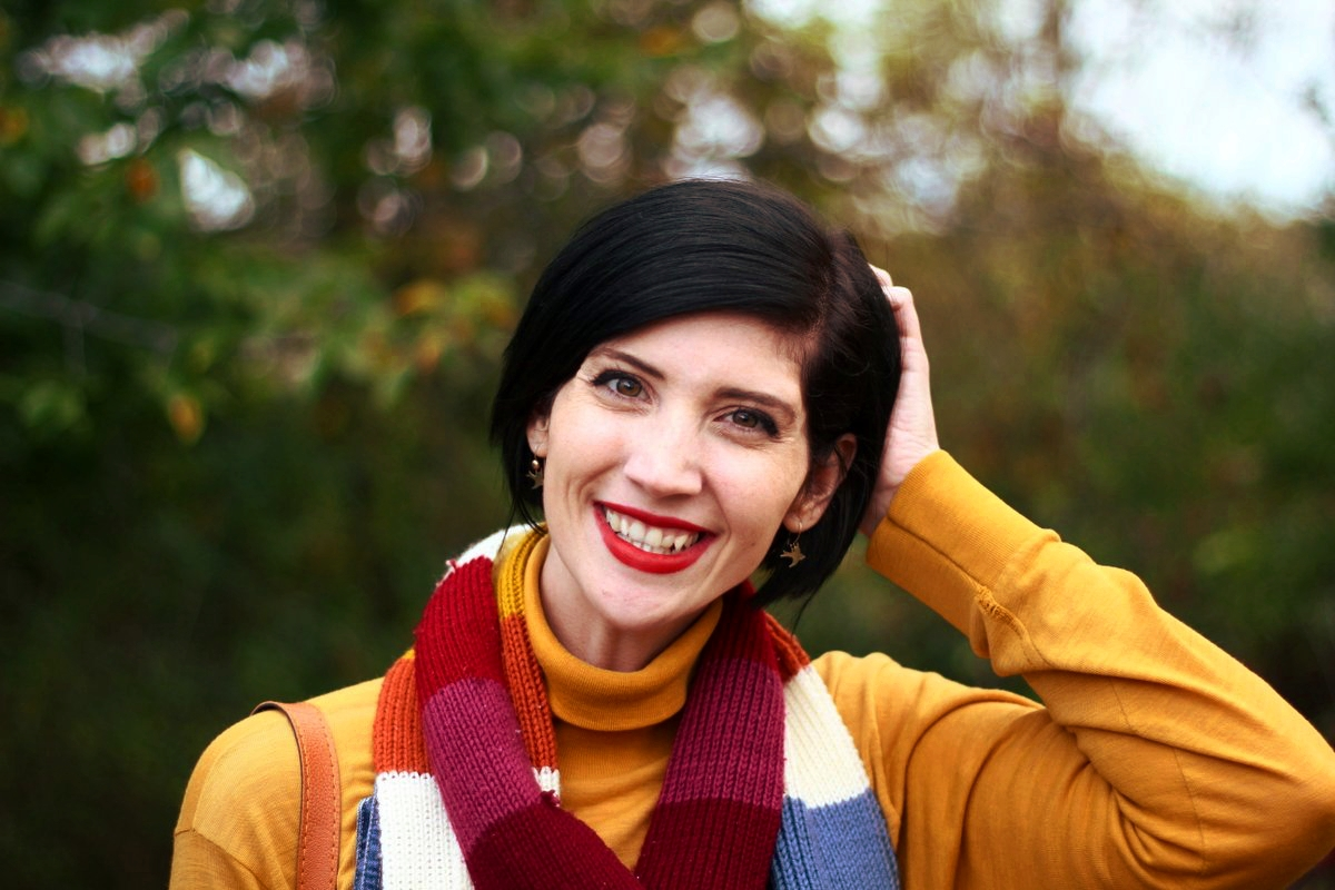 Outfit details: Mustard yellow turtleneck, denim overall dress, multi-colored striped scarf, red lipstick