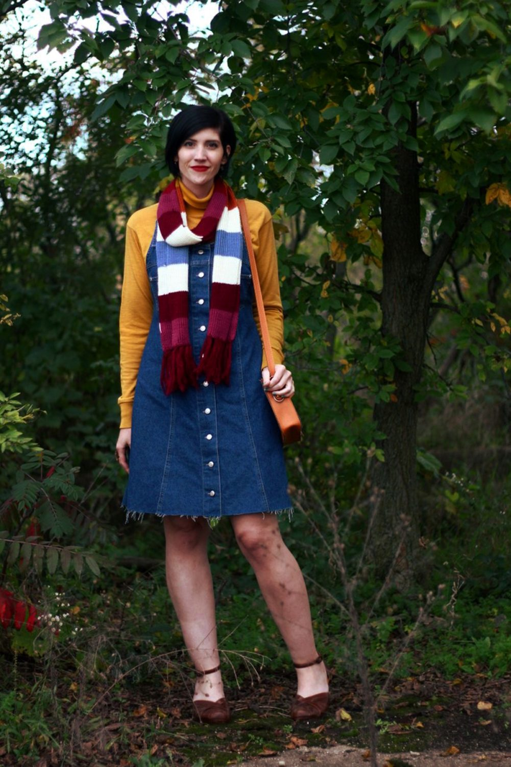 Outfit: Mustard yellow turtleneck, denim overall dress, multi-colored striped scarf, red lipstick, orange fox handbag, brown platforms