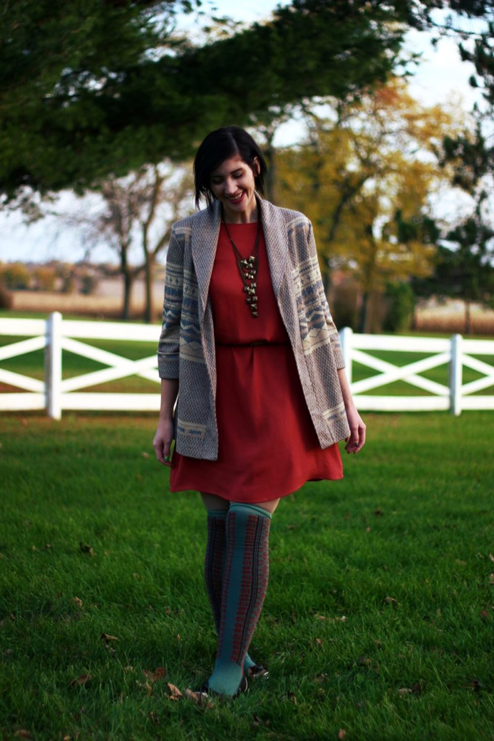 Outfit: Orange dress, beige belt, bronze necklace, patterned cardigan, otk colorful socks, brown flats