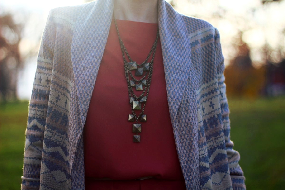 Outfit details: Orange dress, bronze necklace, patterned cardigan